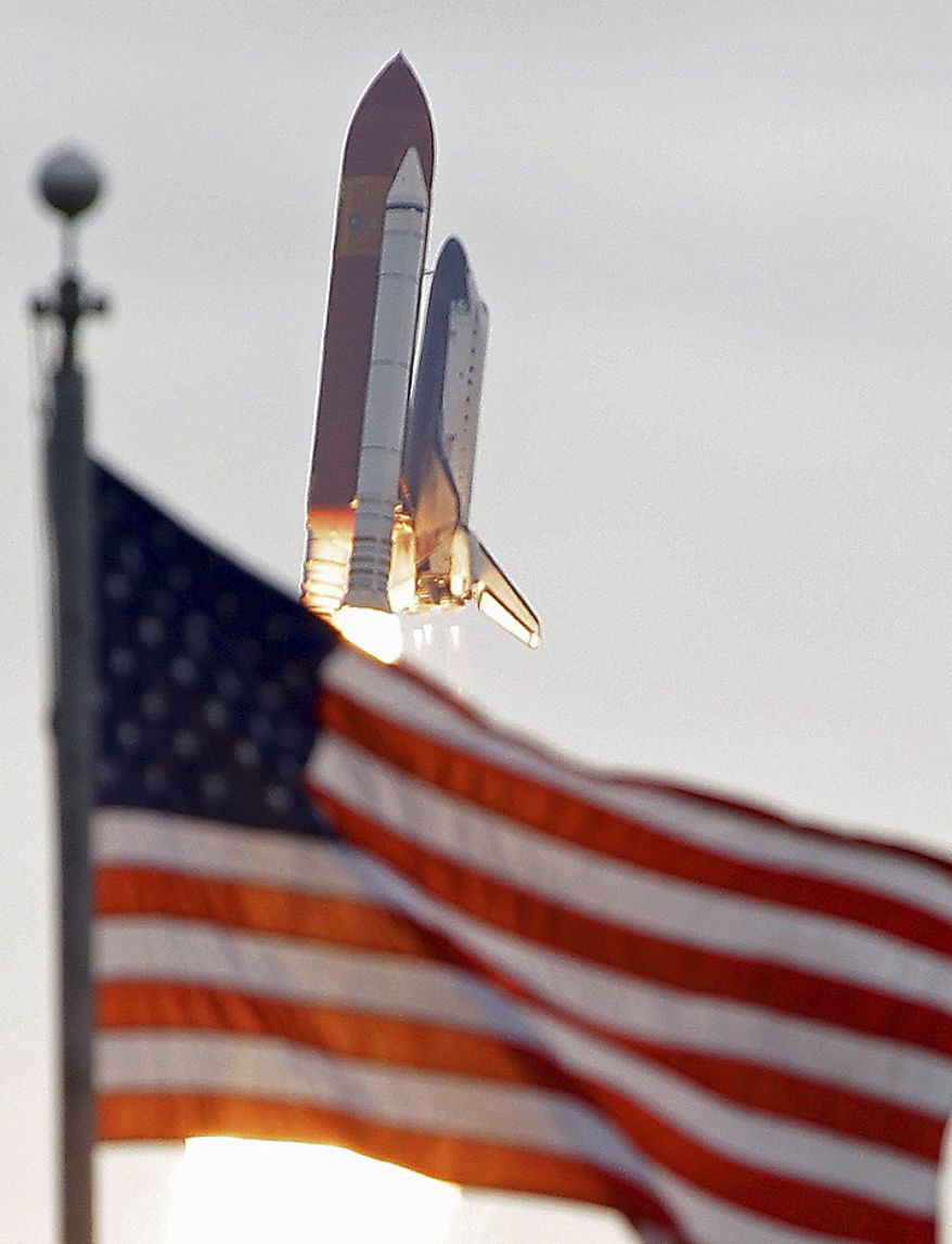Space shuttle Endeavour flies past the US Flag after launch at Cape Canaveral, Fla., on Monday, May 16, 2011.  (AP Photo/John Raoux)