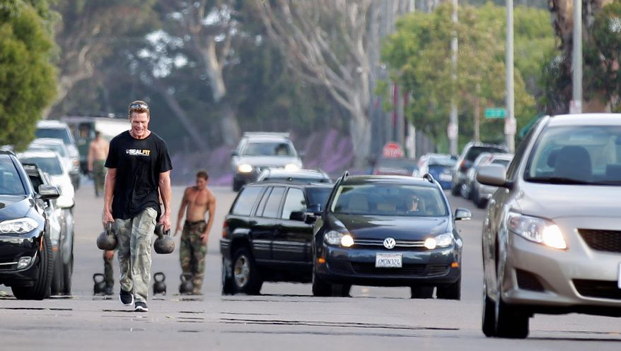ASSOCIATED PRESS Men race walk through traffic carrying kettlebells as part of a workout designed to mirror Navy SEAL training at the SEALFIT exercise center in Encinitas, Calif. Since a SEAL team's takedown of Osama bin Laden, interest is growing in fitness programs run by former members of the elite force.