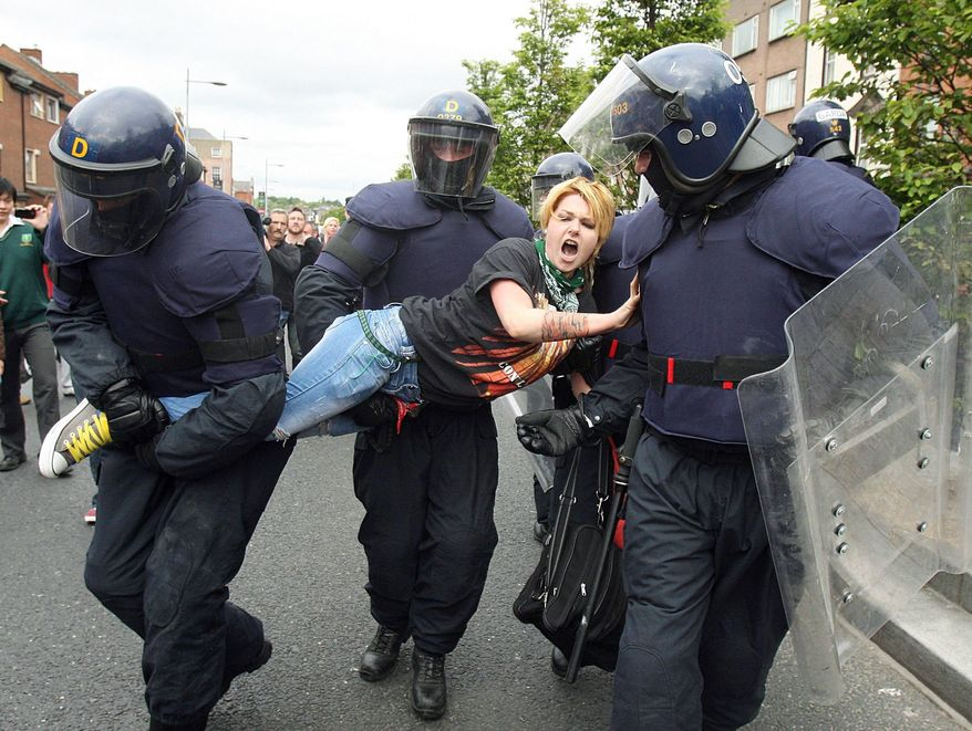 ASSOCIATED PRESS PHOTOGRAPHS A protester is stopped by police in a street in Dublin on Tuesday during a demonstration against the first-ever visit to Ireland of Britain's Queen Elizabeth II. The Queen set foot on Irish soil at the start of a historic state visit that will herald a new era in relations between Britain and Ireland.