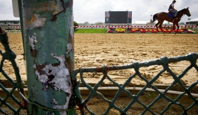 ROD LAMKEY JR./THE WASHINGTON TIMES HARD TIMES: A horse makes its way around the Pimlico track ringed by rust, chipped paint and a broken fence just days before the 136th running of the Preakness Stakes, the lone highlight remaining for Maryland's thoroughbred racing industry.