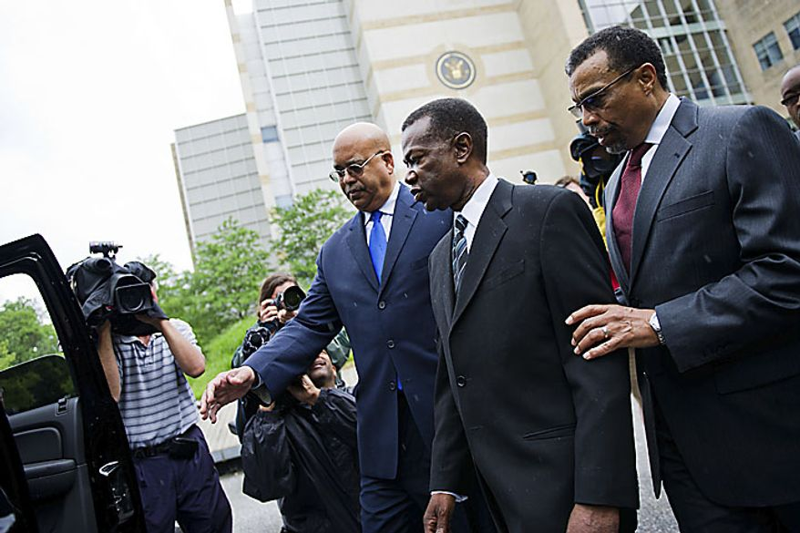 Former Prince George's County Executive Jack B. Johnson heads to his car after leaving the U.S. Federal Courthouse, in Greenbelt, Md., Tuesday, May 17, 2011. Johnson pleaded guilty to one count of extortion and one count of witness tampering. At right is his lawyer Billy Martin. (Drew Angerer/The Washington Times)