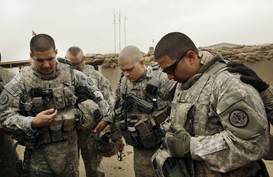 ** FILE ** U.S. Army Lt. Daniel McCord (left), Staff Sgt. Marc Krugh (center) and Sgt. Christopher Torrentes of the 3rd Armored Cavalry Regiment pray before heading out on a patrol at Contingency Operating Site Kalsu, south of Baghdad, Iraq, on Tuesday, Jan. 25, 2011. (AP Photo/Maya Alleruzzo, File)
