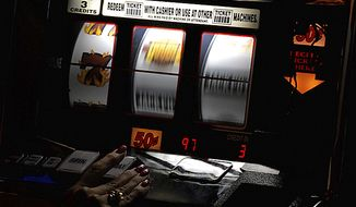 A patron tries her luck at a slot machine. ( Peter Lockley / The Washington TImes )