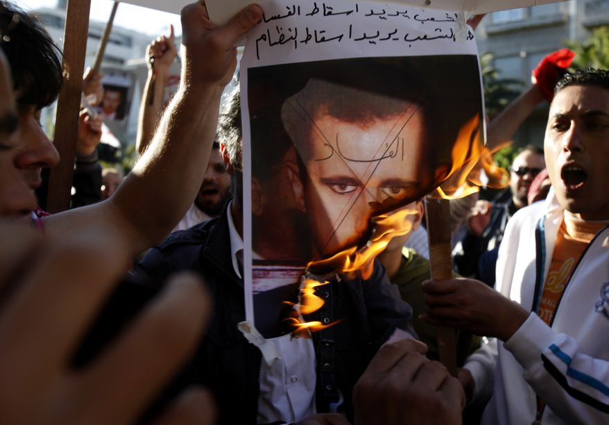 Protesters burn a picture of Syrian President Bashar al-Assad with 'Corruption' written across his face during a protest in central Athens on May 13, 2011. (Associated Press)