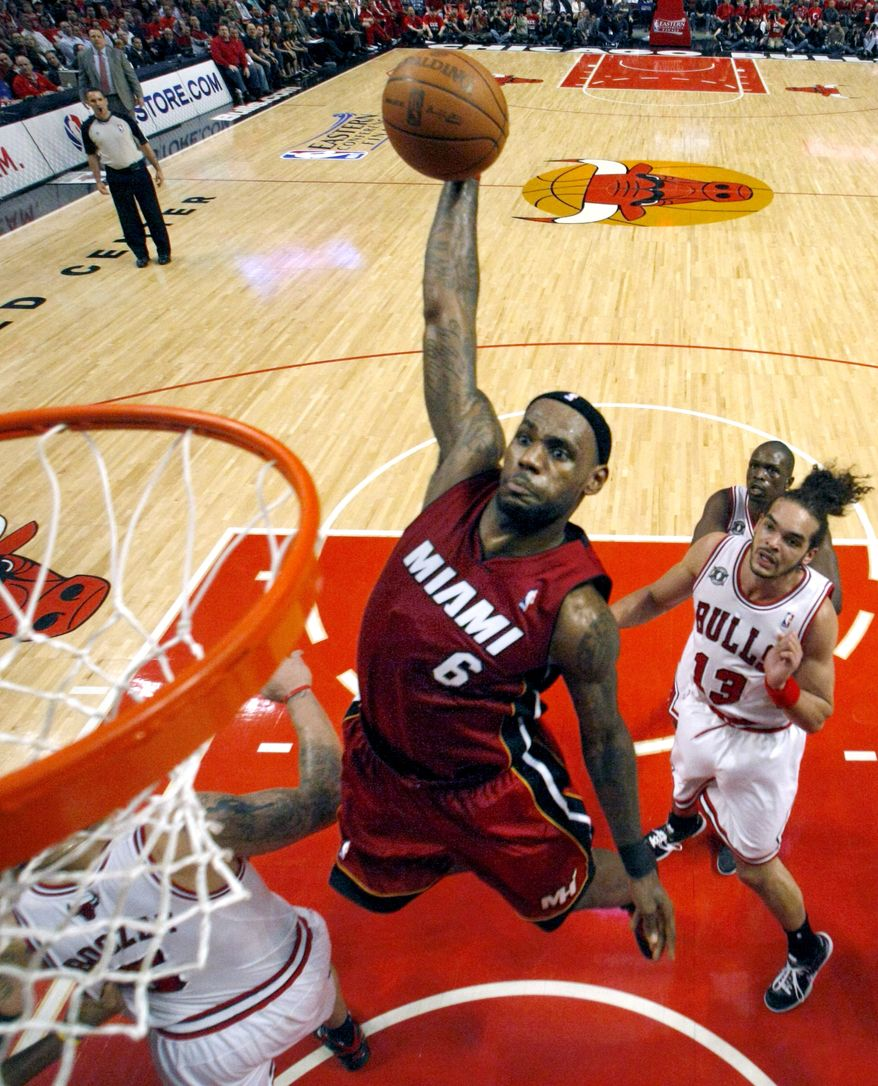 Miami Heat forward LeBron James (6) dunks over Chicago Bulls forward Carlos Boozer, left, and center Joakim Noah during the first quarter of Game 2 of the NBA basketball Eastern Conference finals on Wednesday, May 18, 2011, in Chicago. (AP Photo/Charlie Arbogast)