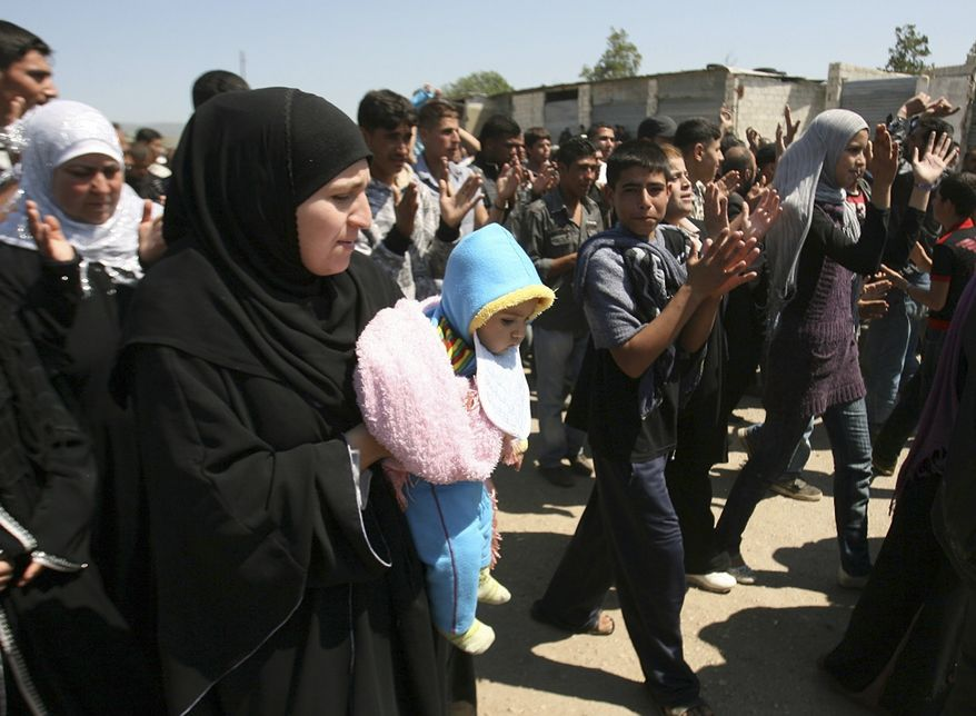Syrians who fled violence in their country's western villages along the Lebanese-Syrian border protest Syrian President Bashar Assad and his regime during a demonstration in the Wadi Khaled area of Lebanon on Monday, May 16, 2011. (AP Photo)