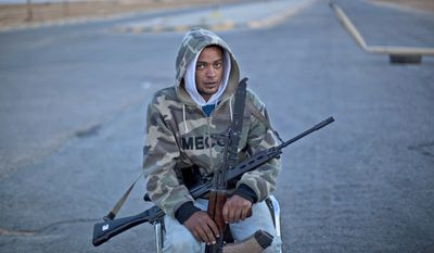 Libyan rebel fighter Yamen Saad, 28, pulls security duty at the last checkpoint that allows the presence of reporters before the front line in Ajdabiya, Libya, on Tuesday, May 17, 2011. (AP Photo/Rodrigo Abd)