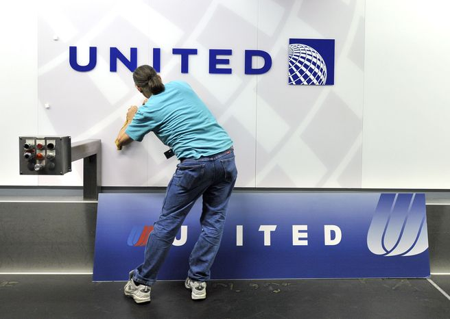 Steve Reininger removes a sign with the old United Airlines logo to reveal the new logo featuring the Continental Airlines blue globe at a ticket counter at O'Hare International Airport on May 17, 2011. (Associated Press)