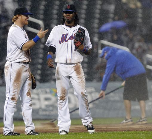 New York Mets' Justin Turner, left, and Jose Reyes talk before the top of the eighth inning as the grounds crew tries to dry the field a bit during a baseball game against the Washington Nationals at Citi Field in New York, Wednesday, May 18, 2011. The Mets won 3-0. (AP Photo/Paul J. Bereswill)