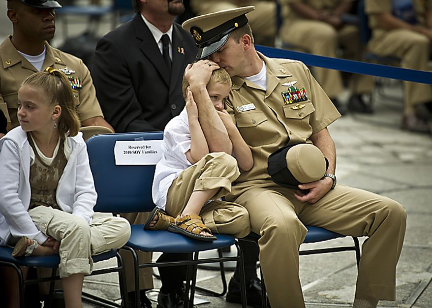 USN PRC(AW/SW/FPJ) David B. Davis holds his six year-old son Tristan as he waits to watch his wife USN PR1 (AW/SW) Amy E. Davis receive her award during the Sailor of the Year 2010 ceremony at the U.S. Navy Memorial in Washington, D.C., Thursday, May 19, 2011. The Sailor of the Year program began in 1972 to recognize the outstanding Sailors of the Atlantic and Pacific Fleets. (Rod Lamkey Jr./The Washington Times)