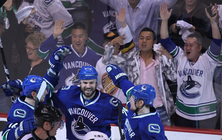 Vancouver Canucks' Aaron Rome, center, celebrates his goal with teammates Alex Burrows, left, and Christian Ehrhoff, of Germany, against the San Jose Sharks during the third period of Game 2 of the NHL hockey Stanley Cup playoffs Western Conference finals, Wednesday, May 18, 2011, in Vancouver, British Columbia. (AP Photo/The Canadian Press, Jonathan Hayward)