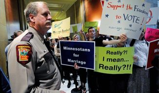 A state trooper stands by as demonstrators on both sides of the gay-marriage issue gathered outside the Minnesota House on Thursday in St. Paul, Minn. Lawmakers cleared the way Saturday night for a voter referendum on the matter. (Associated Press)