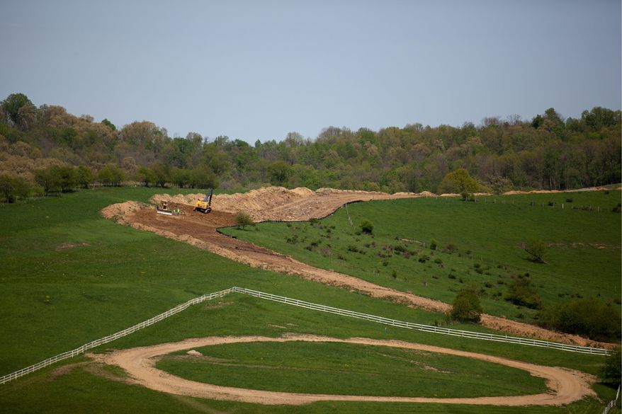 ** FILE ** Dirt is moved over a water pipeline that will be used at a natural gas drilling site in Washington, Pa. Proponents of extracting natural gas from shale tout fracking as the key to satisfying the nation's booming energy appetite.  (Andrew S. Geraci/The Washington Times)