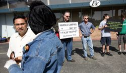 The Rev. Jacob Denys (left) rallies members of his Calvary Bible Church of Milpitas, Calif., outside the closed Family Radio International headquarters of media mogul Harold Camping on Saturday, May 21, 2011, in Oakland, Calif. (AP Photo/Dino Vournas)