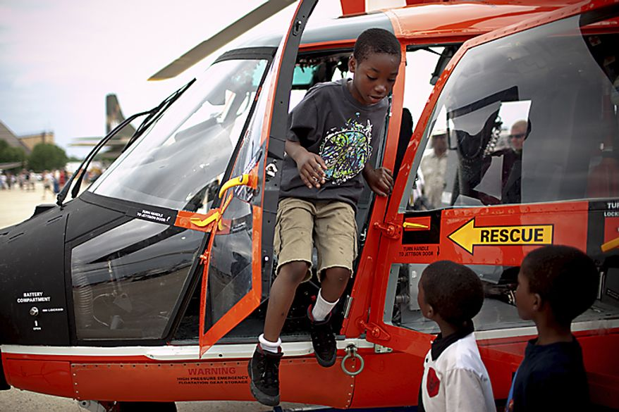 Yalen Murphy, 9, of Temple Hills, Md., hops out of a U.S. Coast Guard Helicopter after sitting at the controls, during the Open House and Air Show at Andrews Air Force Base, Sunday, May 22, 2011. (Drew Angerer/The Washington Times)