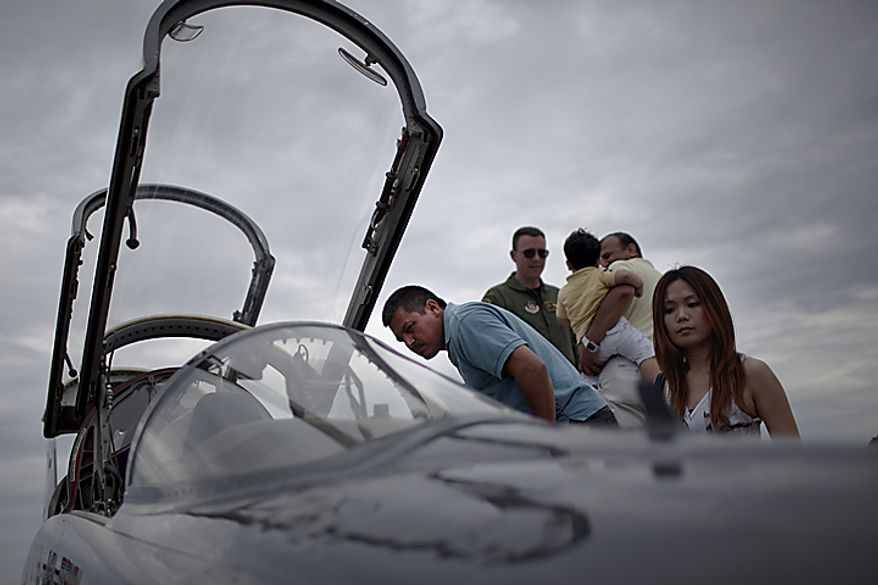Juan Sanchez, center, checks out the cockpit of an Air Force jet during the Open House and Air Show at Andrews Air Force Base, Sunday, May 22, 2011. (Drew Angerer/The Washington Times)