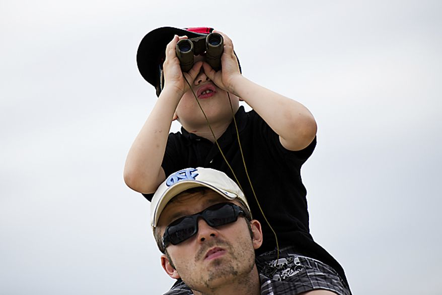 Tyler McCoy, 5, of Silver Spring, sits on top of his dad Shannon McCoy's shoulders to get a better look at the planes, during the Open House and Air Show at Andrews Air Force Base, Sunday, May 22, 2011. (Drew Angerer/The Washington Times)