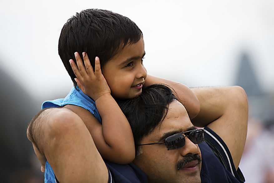 Arvit Sanghi, 5, covers his ears as the U.S. Air Force Thunderbirds fly loudly over him during the Open House and Air Show at Andrews Air Force Base, Sunday, May 22, 2011. (Drew Angerer/The Washington Times)