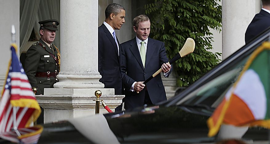 President Barack Obama, is shown how to hold a hurling stick by Ireland's Taoiseach Enda Kenny, in front of  Farmleigh House in Dublin, Ireland, Monday, May 23, 2011. (AP Photo/Carolyn Kaster)