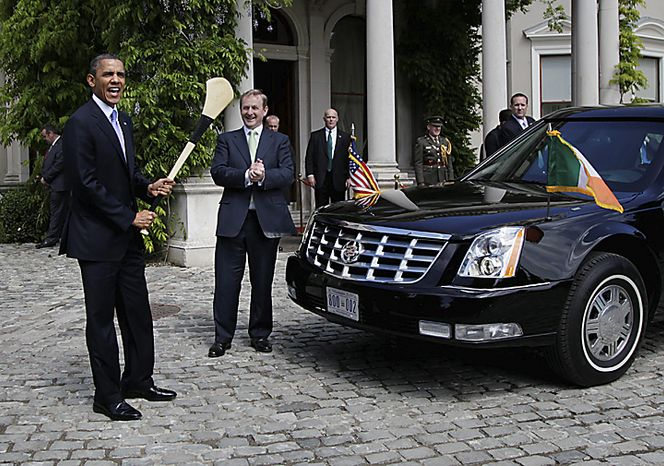 President Barack Obama, left, holds and swings a hurling stick as Ireland's Taoiseach Enda Kenny, second from left, looks on he and first lady Michelle Obama leave Farmleigh House after after a visit in Dublin, Ireland, Monday, May 23, 2011. President Barack Obama opens a six-day European tour with a quick dash through Ireland, where he will celebrate his own Irish roots and look to give a boost to a nation grappling with the fallout from its financial collapse.(AP Photo/Carolyn Kaster)