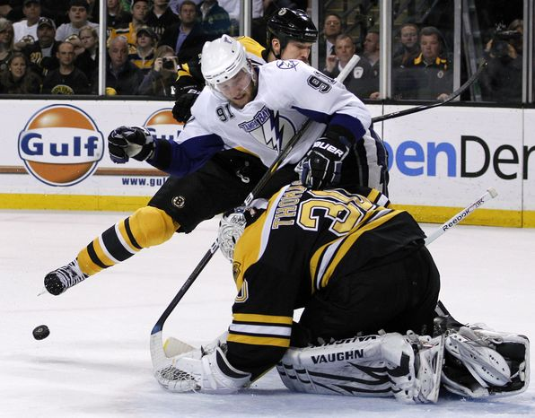 Tampa Bay Lightning center Steven Stamkos (91) is prevented from scoring by Boston Bruins defenseman Andrew Ference, behind, and goalie Tim Thomas (30) in the first period of Game 5 of the NHL hockey Stanley Cup playoffs Eastern Conference finals, in Boston on Monday, May 23, 2011. (AP Photo/Elise Amendola)