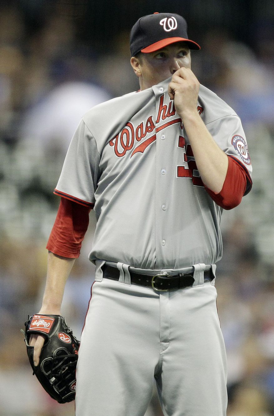 Washington Nationals starting pitcher Tom Gorzelanny wipes his face after giving up a two-run home run to Milwaukee Brewers' Corey Hart during the fifth inning of a baseball game Monday, May 23, 2011, in Milwaukee. (AP Photo/Morry Gash)