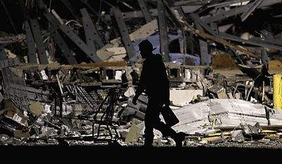 ** FILE ** An emergency worker searches a tornado-damaged Walmart store in Joplin, Mo., on Monday, May 23, 2011. A large tornado moved through much of the city Sunday, damaging a hospital and hundreds of homes and businesses. (AP Photo/Charlie Riedel)