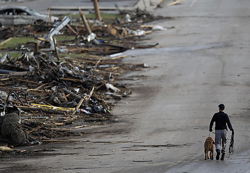A rescue worker walks past debris at Joplin High School in Joplin, Mo., on Monday, May 23, 2011. A large tornado moved through much of the city Sunday, severely damaging the school, a hospital, and hundreds of homes and businesses. The twister killed at least 89 people. (AP Photo/Charlie Riedel)