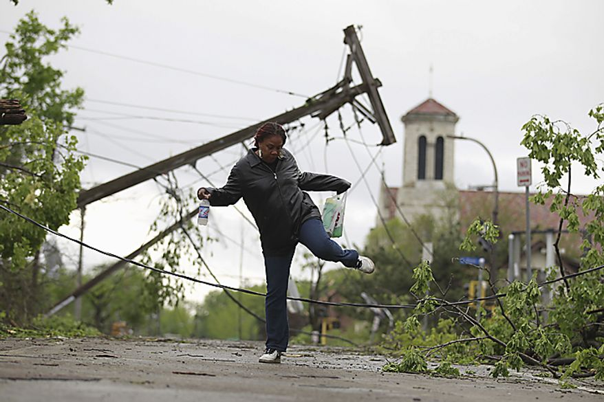 Lynn Mosley carefully steps over downed power lines on Monday, May 23, 2011, in north Minneapolis, the morning after a tornado ripped a nearly five-mile path from suburban St. Louis Park through north Minneapolis, tearing roofs off houses, toppling huge trees and power lines and knocking over rail cars in the northern suburb of Fridley. (AP Photo/The Star Tribune, Jerry Holt)