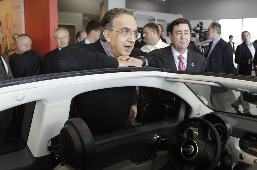 Chrysler CEO Sergio Marchionne leans on a Fiat 500 cabriolet at the opening of the Fiat of Lakeside dealership in Macomb Township, Mich., on Monday, May 23, 2011. (AP Photo/Carlos Osorio)