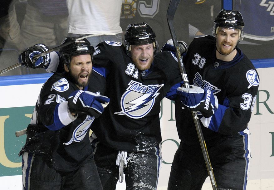 NHL Playoffs: Tampa Bay Lightning's Martin St. Louis (26) celebrates his second goal with teammates Steven Stamkos (91) and Mike Lundin (39) during the third period in Game 6 of an NHL hockey Stanley Cup playoffs against the Boston Bruins in the Eastern Conference final series in Tampa, Fla., Wednesday, May 25, 2011. Tampa Bay won 5-4. (AP Photo/Phelan M. Ebenhack)