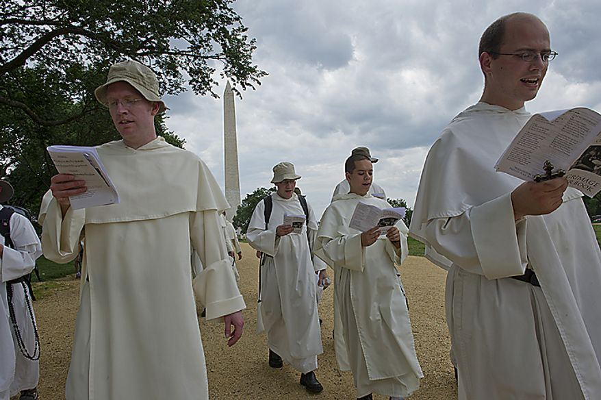 Catholic friars from the Dominican order sing hymns and say prayers as they walk along the National Mall in Washington on Tuesday, May 24, 2011, on their pilgrimage from the Dominican House of Studies in Northeast Washington to St. Dominic's Parish in Southwest. This is the first time the friars have held the pilgrimage, which commemorated the date that St. Dominic's body was moved from its original grave to its current resting place in Bologna, Italy. (Barbara L. Salisbury/The Washington Times)