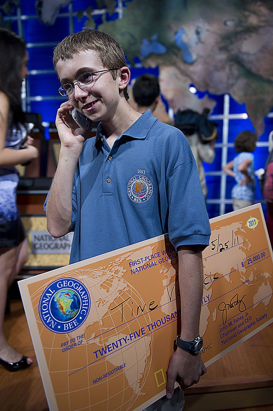 National Geographic Bee 2011 champion Tine Valencic, 13, from Coleyville, Texas, smiles as he talks on the phone with his father (who was at home and couldn't make it to the final round in Washington, D.C., on Wednesday, May 25, 2011) telling him he won. In his hand Tine holds the winning check, a $25,000 scholarship. Although he has already taken the ACT college entrance exam and scored a 32 out of 36, Tine says he still has five years to decide where he wants to go to college and what he wants to study. (Barbara L. Salisbury/The Washington Times)