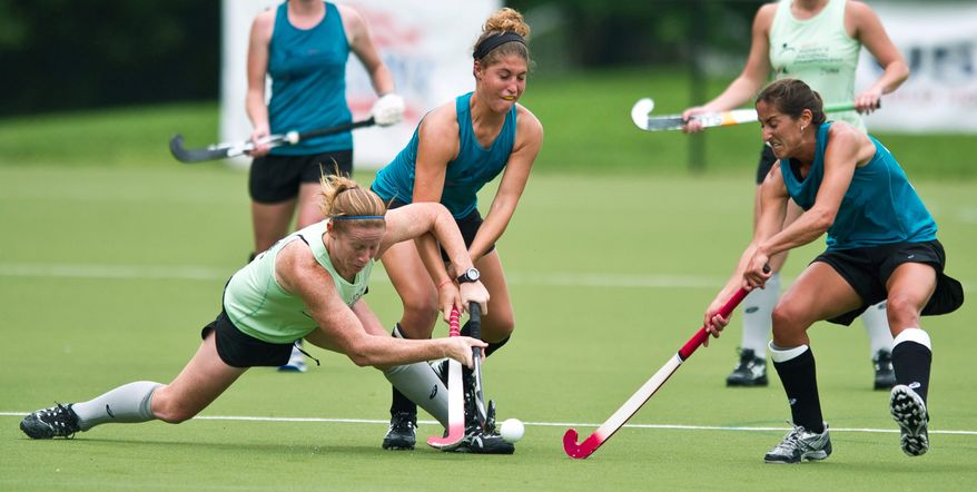 Maxine Fluharty (#2, center) and Dina Rizzo (#12, right) of Mid Atlantic put the pressure on as Claire Llaubach (#21, left) of Pennsylvania falls to the ground in the second half during the USA Field Hockey Women's National Championship at American University on May 20, 2011. Pennsylvania went on to win 1-0. (Rod Lamkey Jr./The Washington Times)