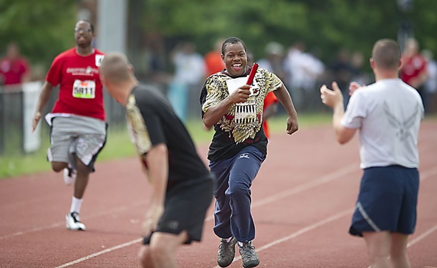 Daishaun Howell (center) races to get the baton to Army SSG. Tanner Welch in the Unified 4x100 meter relay during the 2011 Special Olympics D.C. Summer Games being held at Catholic University in Washington, D.C., Wednesday, May 25, 2011. (Rod Lamkey Jr./The Washington Times)