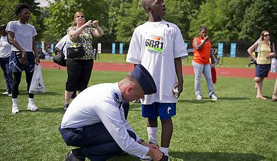 Air Force Col. Tony Thomas (left) helps tie the shoes of runner Javon McCray (right) prior to his running in the Unified 4x100 meter relay during the 2011 Special Olympics D.C. Summer Games being held at Catholic University in Washington, D.C., Wednesday, May 25, 2011. (Rod Lamkey Jr./The Washington Times)