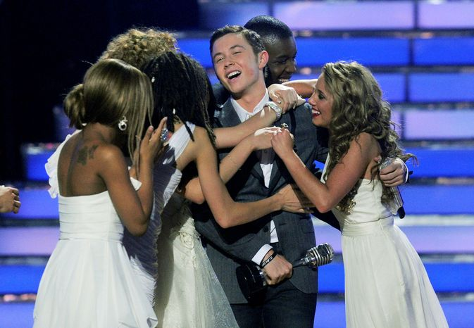 """ASSOCIATED PRESS Scotty McCreery is embraced by fellow contestants after winning the 10th season of """"American Idol."""" The 17-year-old bested Lauren Alaina, 16,"""