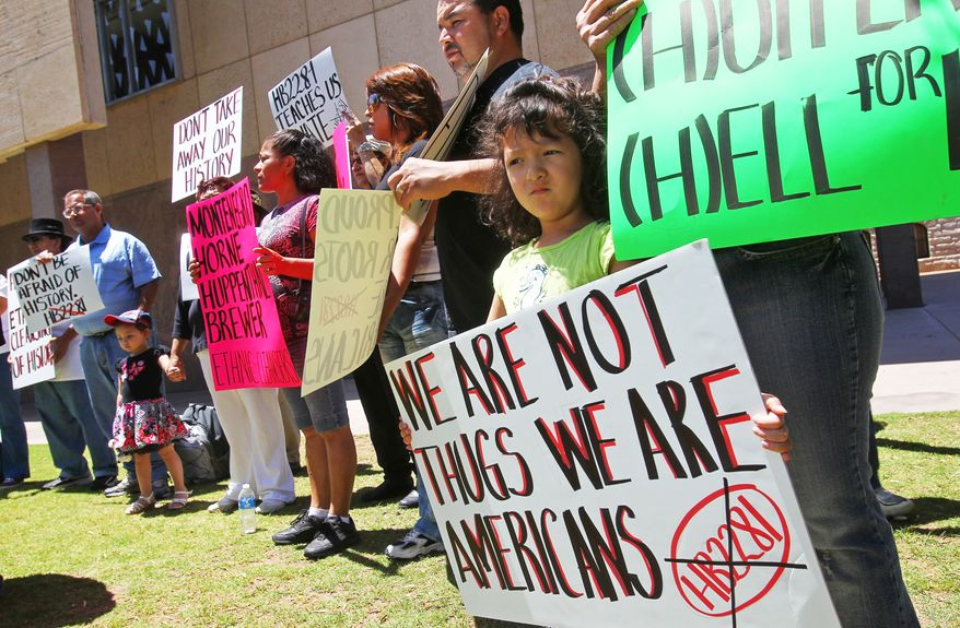 **FILE** Miroslava Acosta, 4, holds a sign during a rally at the Arizona state capital building in Phoenix on May 9, 2011, to protest Arizona's decision to appeal to the U.S. Supreme Court a decision by a lower court that put the most controversial parts of the state's immigration enforcement law on hold. (Associated Press)