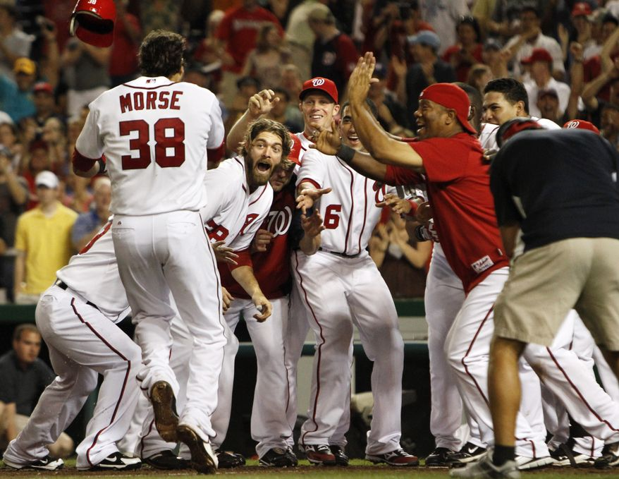 Washington Nationals first baseman Michael Morse throws his batting helmet in the air as he is cheered by teammates after hitting a walk-off home run against the San Diego Padres on Friday, May 27, 2011. The Nationals won 2-1. (AP Photo/Jacquelyn Martin)