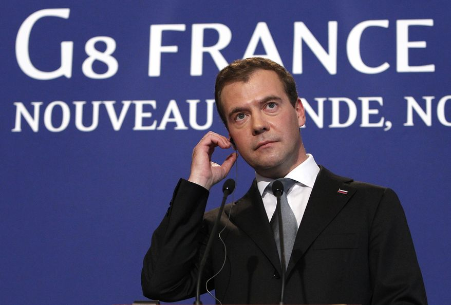 Russian President Dmitry Medvedev adjusts his earpiece during a press conference at the G8 summit in Deauville, France, Friday, May 27, 2011. Medvedev says he's sending his special envoy to hold talks with Libyan rebels in Benghazi. (AP Photo/Alexander Zemlianichenko)