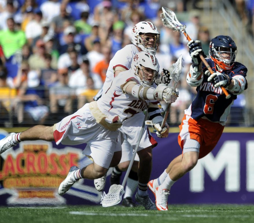 NCAA lacrosse: Virginia's Steele Stanwick, right, shoots and scores as Denver's Henry Miketa, front left, defends during the first half of an NCAA college men's Division I lacrosse semifinal game on Saturday, May 28, 2011, in Baltimore. Stanwick recorded three goals and two assists in Virginia's 14-8 victory over Denver. (AP Photo/Gail Burton)