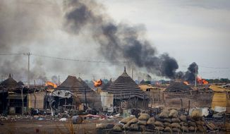 Homesteads continue to burn in the center of Abyei, a Sudanese border town, on Saturday. Tens of thousands of Sudanese are fleeing from the contested north-south border region of Abyei, and the top U.S. official in the region warned Friday of a humanitarian crisis over the north's invasion. (Associated Press)
