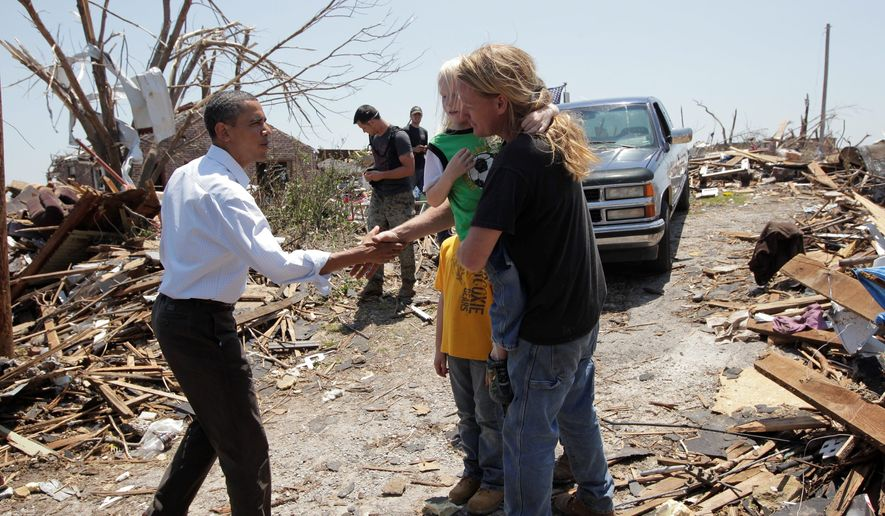 President Barack Obama, left, reaches out to residents while viewing damage from the tornado that devastated Joplin, Mo., Sunday, May 29, 2011. (AP Photo/J. Scott Applewhite)