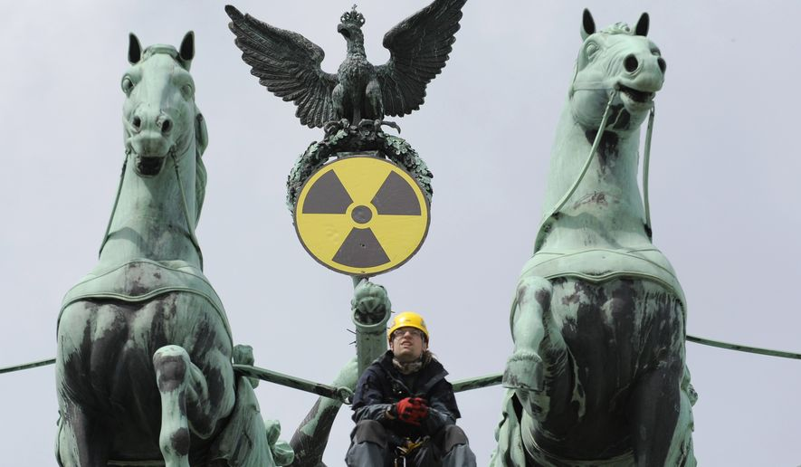 An environmental activist sits atop the Brandenburg Gate in Berlin on Sunday, May 29, 2011, after Greenpeace activists fixed a radioactive sign to the gate's Quadriga sculpture to protest the nuclear power policy of the German government. (AP Photo/dapd/Michael Gottschalk)