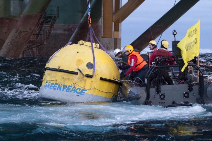 Greenpeace activists secure an arctic survival pod on the underside of the Leiv Eiriksson oil rig off Greenland's coast on Sunday, May 29, 2011, in an attempt to stop a Scottish oil company from starting deepwater drilling in the arctic waters. (AP Photo/Greenpeace, Steve Morgan)