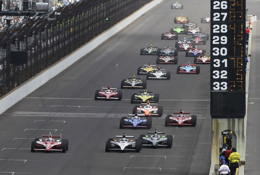 IndyCar driver Scott Dixon (front left) of New Zealand leads the field down the main straightaway on the first double-file restart during the Indianapolis 500 auto race at the Indianapolis Motor Speedway in Indianapolis on Sunday, May 29, 2011. (AP Photo/Paul Sancya)