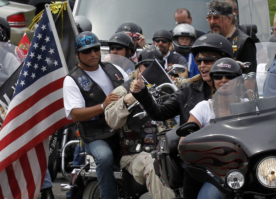Former Alaska Gov. Sarah Palin (second from right), the 2008 GOP vice presidential nominee, gives a thumbs up from the back seat of a motorcycle at the beginning of Rolling Thunder at the Pentagon in suburban Washington on Sunday, May 29, 2011. (AP Photo/Alex Brandon)