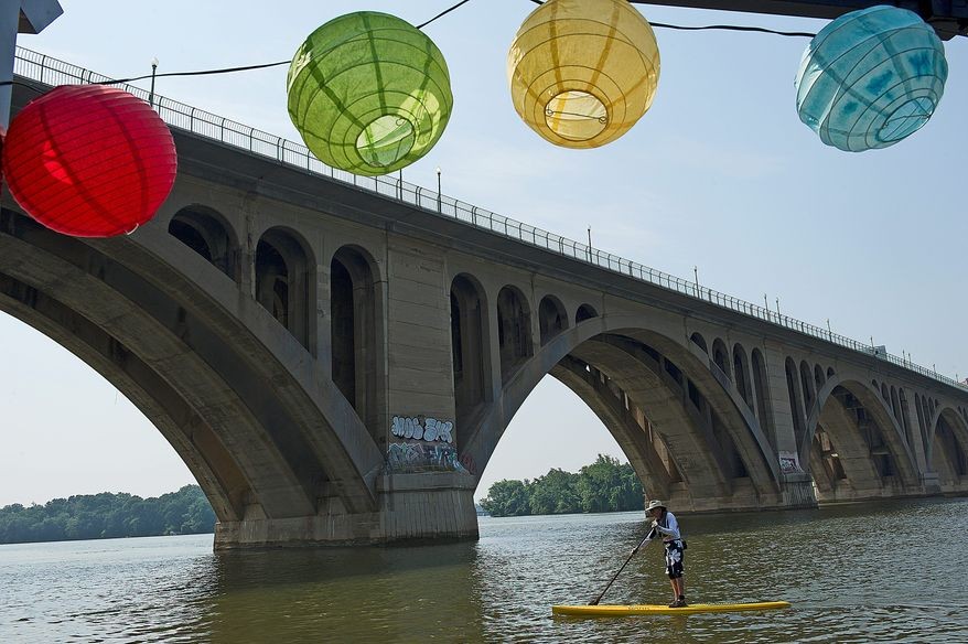 """Mark Baird paddles along the Potomac River near Jack's Boathouse in Georgetown. """"This is so different,"""" he said. """"It feels like I'm getting away with something. The neatest thing is to go out somewhere in the middle of the river and sit down."""" (Barbara L. Salisbury/The Washington Times)"""