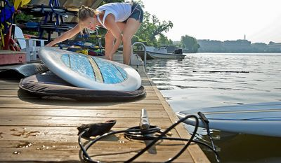 Kathy Summers pulls out a paddle board on the dock at Jack's Boathouse in Georgetown to prepare for an early morning ride on the Potomac River. She's been paddling for about three years and instructs others through her company, Stand Up Paddle DC. (Barbara L. Salisbury/The Washington Times)