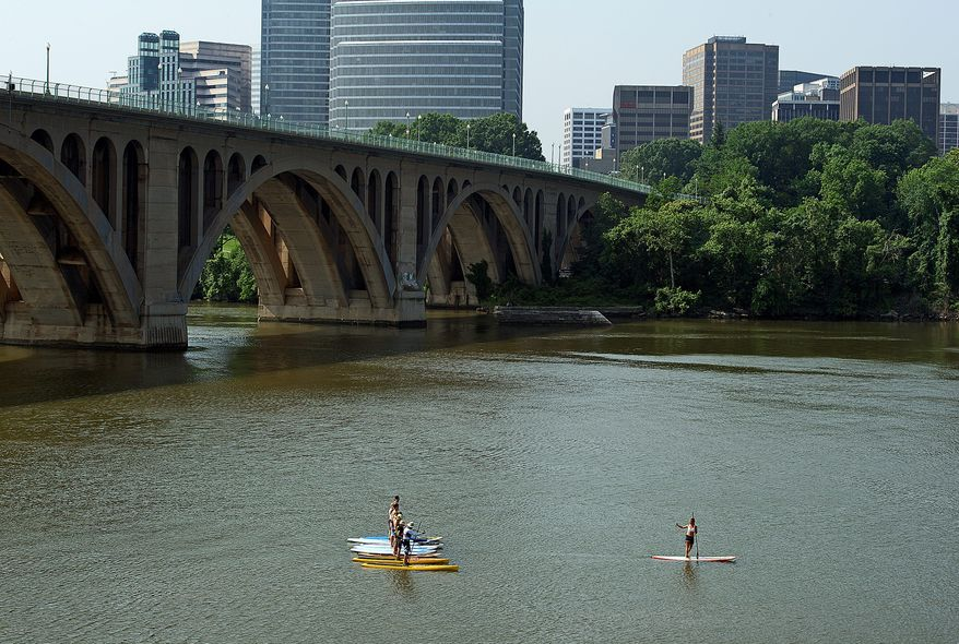 Paddle boarding instructor Kathy Summers (right) lines up a group of her students on the Potomac River below the Francis Scott Key Bridge in Washington. (Barbara L. Salisbury/The Washington Times)